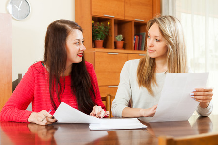 home office interior: women looking  documents at table in home or office interior