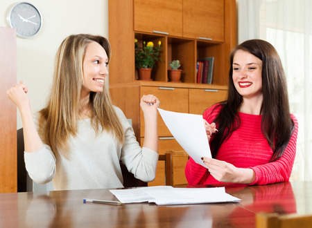 home office interior: Happy girls with  documents  at table in home or office interior