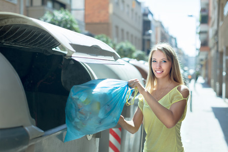 Smiling girl with rubbish near refuse collection container