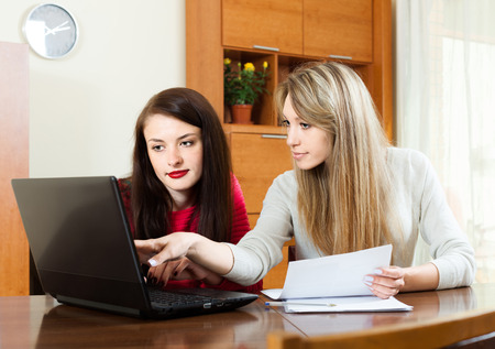 parsimony: business  women with laptop at table in home interior Stock Photo