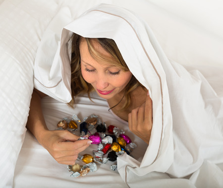 arousing: Smiling female laying in bed with sweets in secret