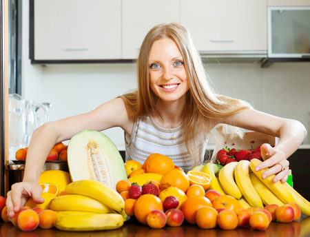 Positive blonde long-haired woman with heap of  fruits in home photo