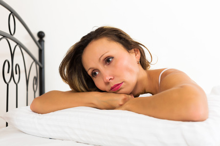 ennui: Sad female with head reclined upon hands in bed