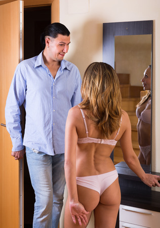 Young woman in sexy lingerie and boyfriend coming home