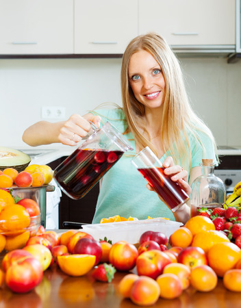 woman pouring beverages with fruits at home kitchen photo