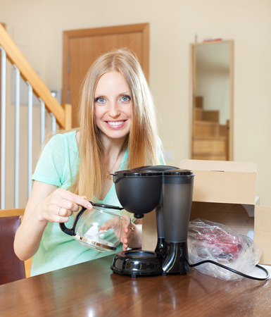 percolator: Young blond with new electric coffee maker at home in living room
