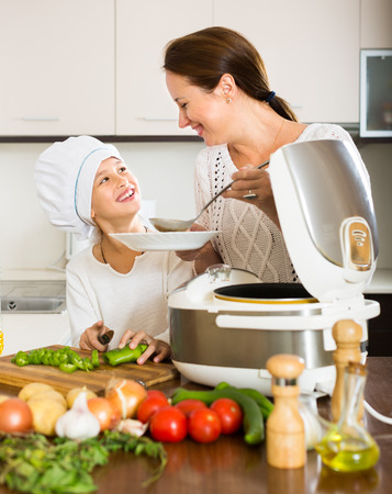 appliances: Happy 25-30 years old mother and little daughter using multicooker at kitchen Stock Photo