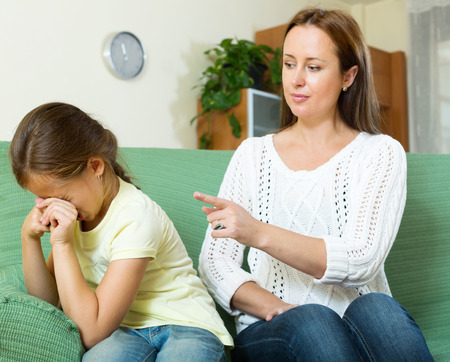 Woman scolding crying child at home interior. Focus on girl