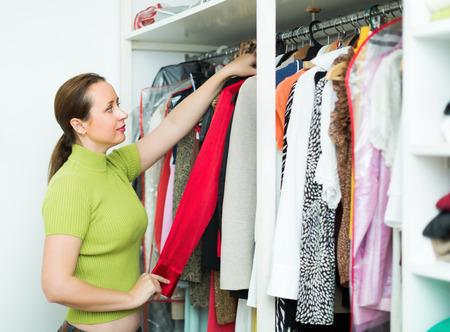 ordelijk: Ordelijke vrouw regelen kleren op kleerkast indoor