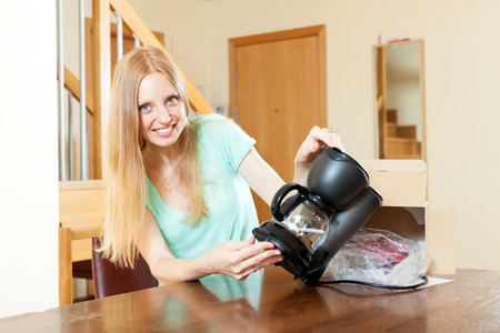 coffeemaker: Smiling young blond unpacking new coffeemaker at home interior Stock Photo