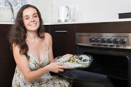 Happy young woman cooking fish in oven at home kitchen
