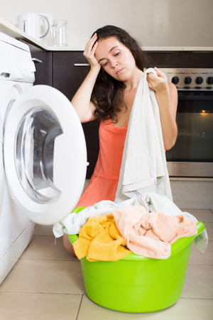 unsatisfactory: Home laundry. Unhappy  girl doing housework at home