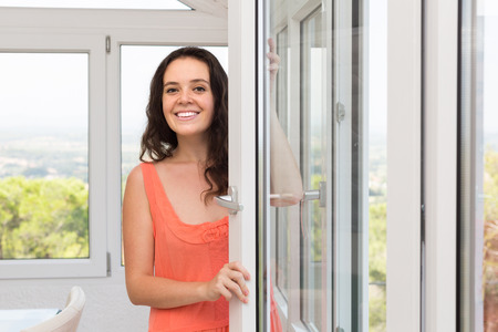 clean window: Beautiful housewife is happy to have new plastic windows Stock Photo