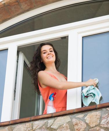 atomizer: Young smiling woman cleaning windows using atomizer