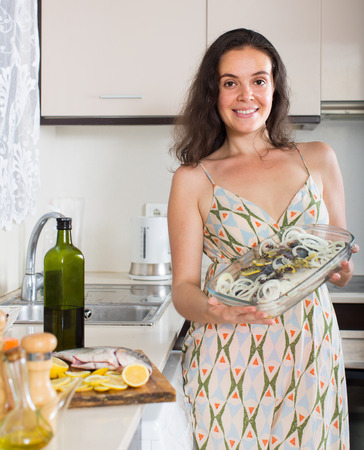 Smiling  girl with raw fish on roasting pan at home kitchen photo