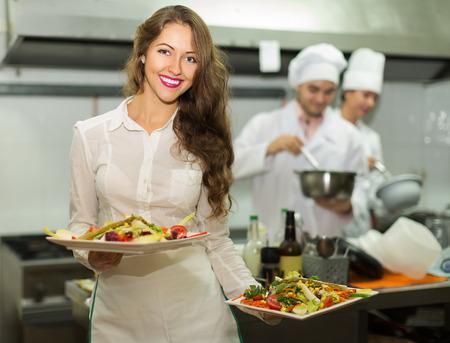 Serveuse prendre des plaques de charme avec repas préparé Banque d'images