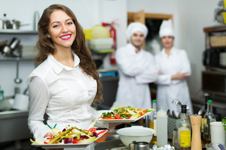 cocinero: Equipo de chefs y hermosa joven camarero en la cocina del restaurante Foto de archivo