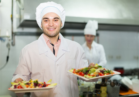 shef: Couple of professional cooks working together at restaurant kitchen. Focus on man