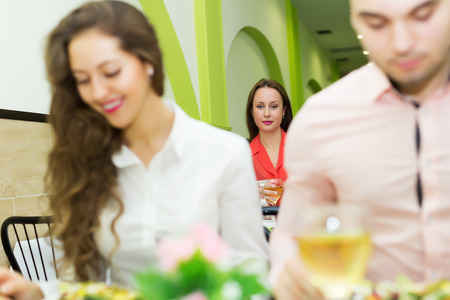 people  having  dinner at the restaurant. Focus on alone woman photo