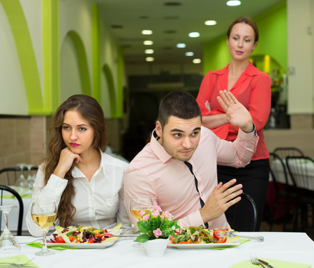 Wife caught husband having dinner in cafe with mistress. Focus on man Stock Photo