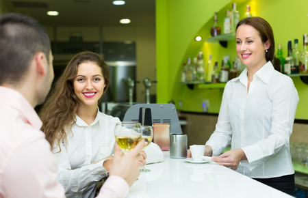 Smiling female barista and two young clients in small bar. Focus on girl photo