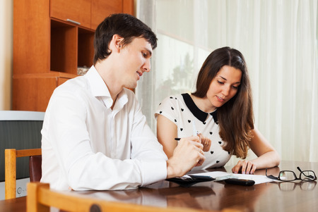 utility payments: Man and woman with money and documents in home interior Stock Photo