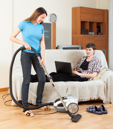 disparity: Girl doing room cleaning while man  with laptop  resting over sofa Stock Photo