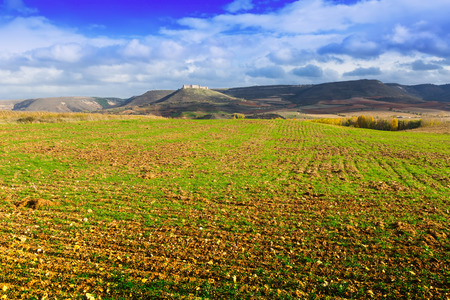 European autumn landscape with stubble fields among hills and castle Stock Photo