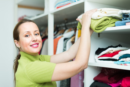 Smiling middle-aged female customer choosing apparel on shelves at store