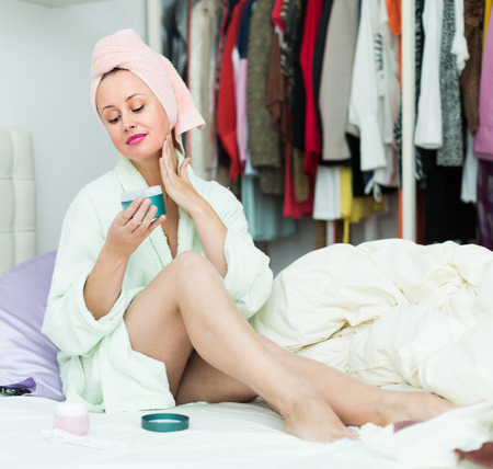 treating: Happy housewife sitting on bed and treating her face skin