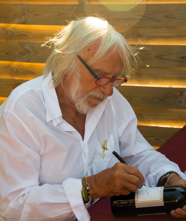 richard: CHATEAU BEL EVEQUE, FRANCE - AUGUST 15, 2014: Pierre Richard signing bottles of self-made wine on the eve of his eightieth birthday Editorial
