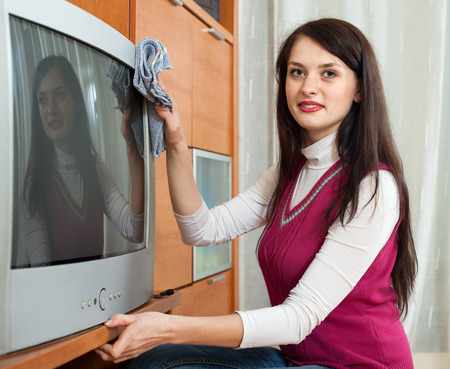 household tasks: Brunette woman wiping the dust on TV at home Stock Photo