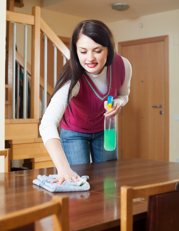 cleanser: brunette girl cleaning table with cleanser and rag in living room at home