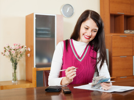 utility payments: brunette housewife calculates the family budget at  home
