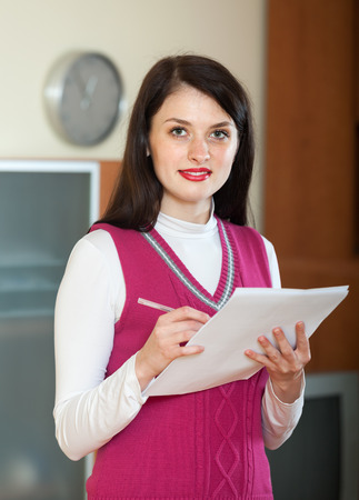 home office interior: Portrait of brunette businesswoman with financial documents at home or office interior