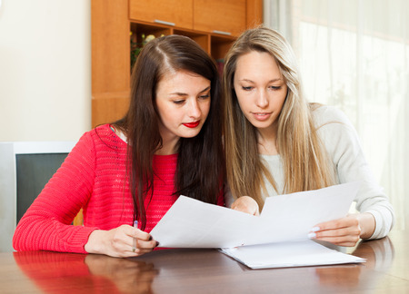 parsimony: women looking financial documents at table in home or office interior