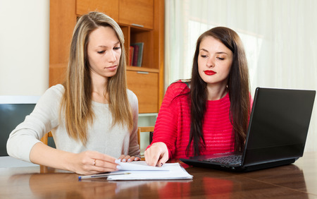 Girls with  documents and notebook at table in home interior photo