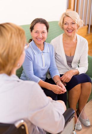 paraplegic: Sonriendo mujeres pensionistas que beben t� con un amigo discapacitado. Enfoque en la mujer izquierda