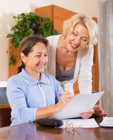 mature woman sitting: Mature females working with documents and smiling. Focus on brunette