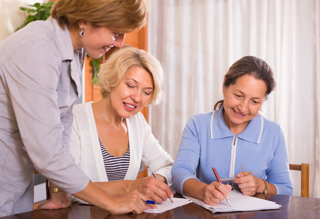 home  life: Two senior ladies signing documents at bank and smiling
