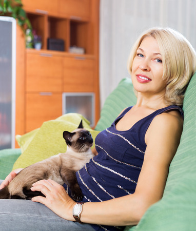 Mature woman playing with Siamese kitten on couch at home photo
