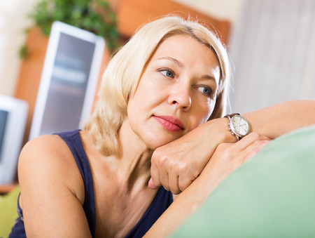 Sad and lonely mature woman sitting on couch at home photo