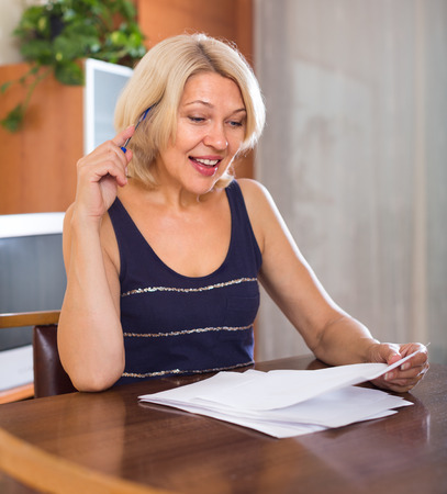 parsimony: Portrait of mature businesswoman with financial documents at office interior Stock Photo