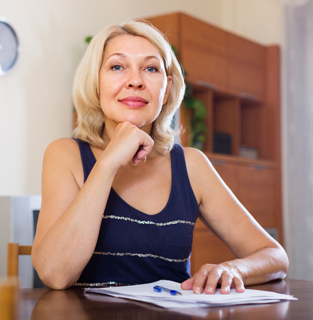 parsimony: quiet mature woman with financial documents at home interior