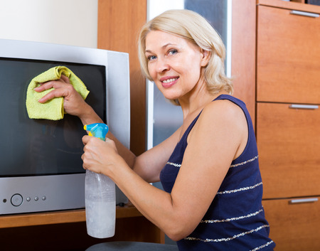 household tasks: mature woman  cleaning  screen of TV with cleanser at home