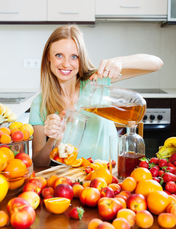cheerful blonde girl pouring fresh beverages with fruits photo