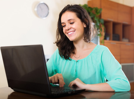 netbook: Young woman looking at netbook in living room