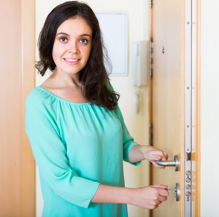 Smiling young housewife trying new lock of front door photo