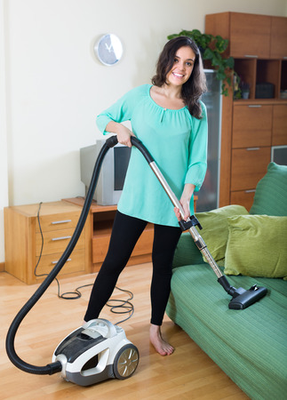 vaccuum: Smiling young brunette woman cleaning living room