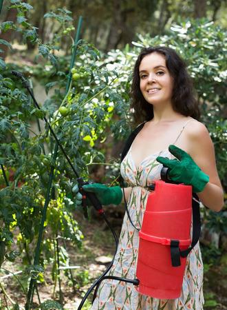 knapsack: Happy girl working in garden with knapsack garden spray Stock Photo